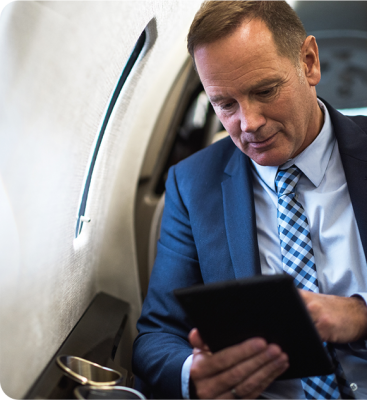 man looking at tablet in airplane